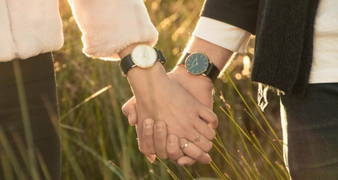 Couple wearing watches holding hands